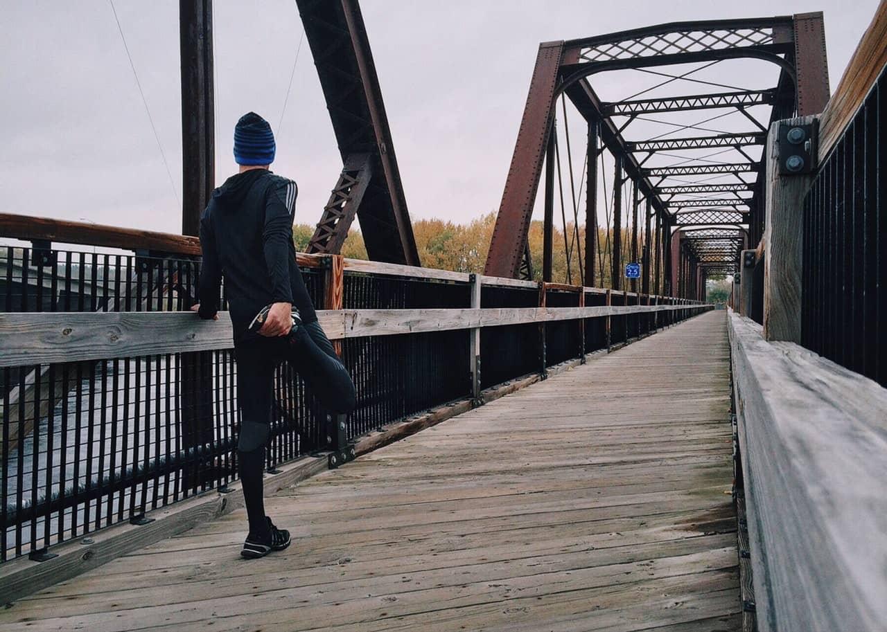 man stretching his legs before a run