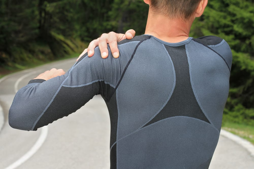 athletic guy holding his shoulder due to arthritis pain.