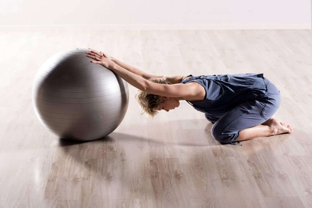 woman stretching her shoulder with an exercise ball