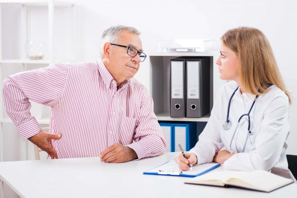 Older male patient speaking to his doctor
