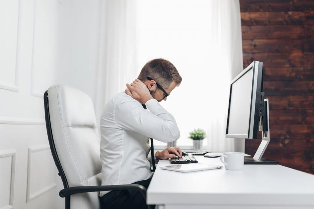 man in his office holding his neck due too neck pain