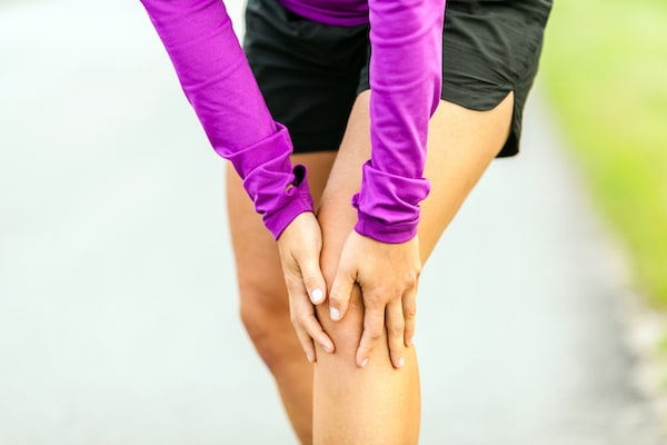 woman holding her knee due to pain after running