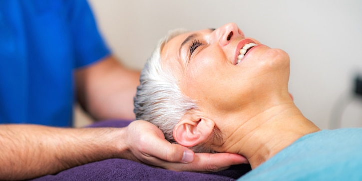 chiropractor massaging female patients neck