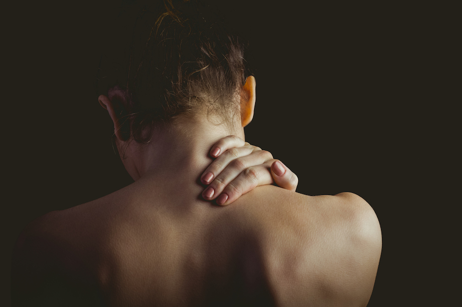 young lady holding her neck due too neck pain