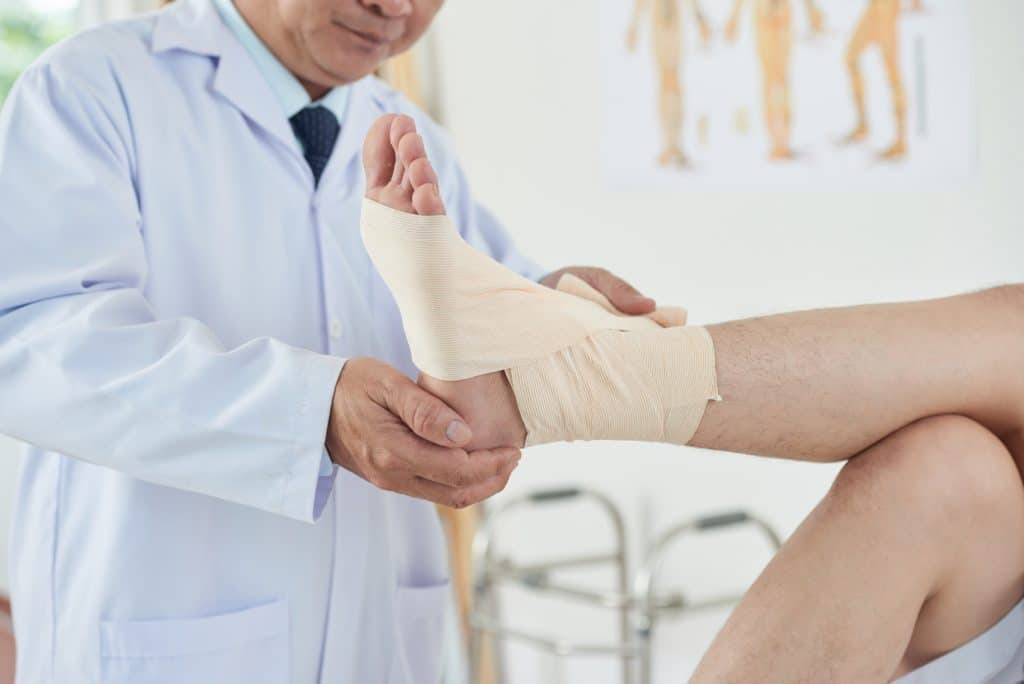 Doctor wrapping a bandage across a patients ankle.