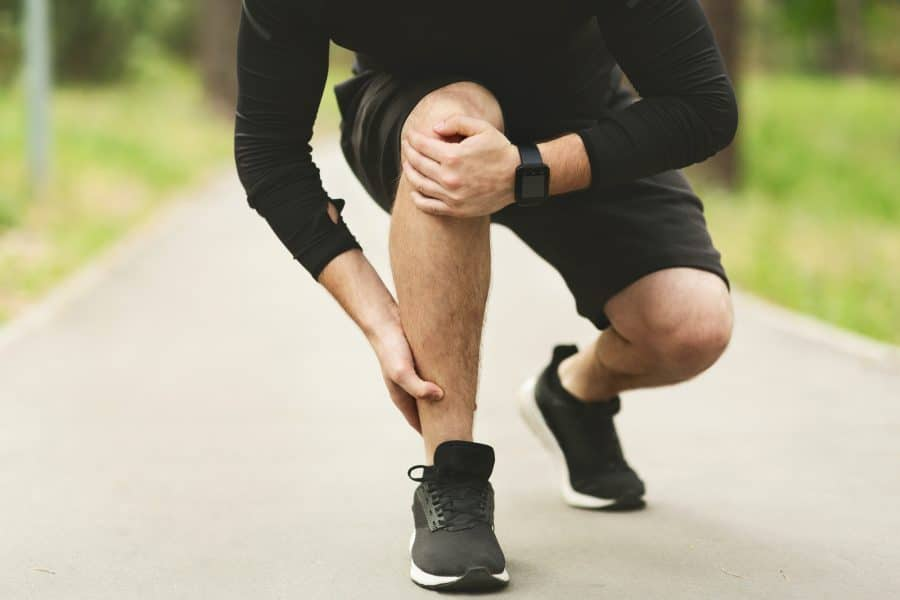 young male runner holding his ankle due to pain