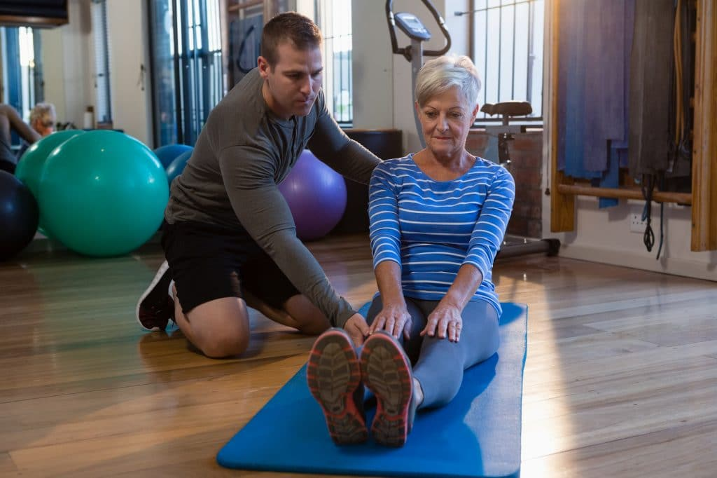 Physical therapist helping his female patient stretch.