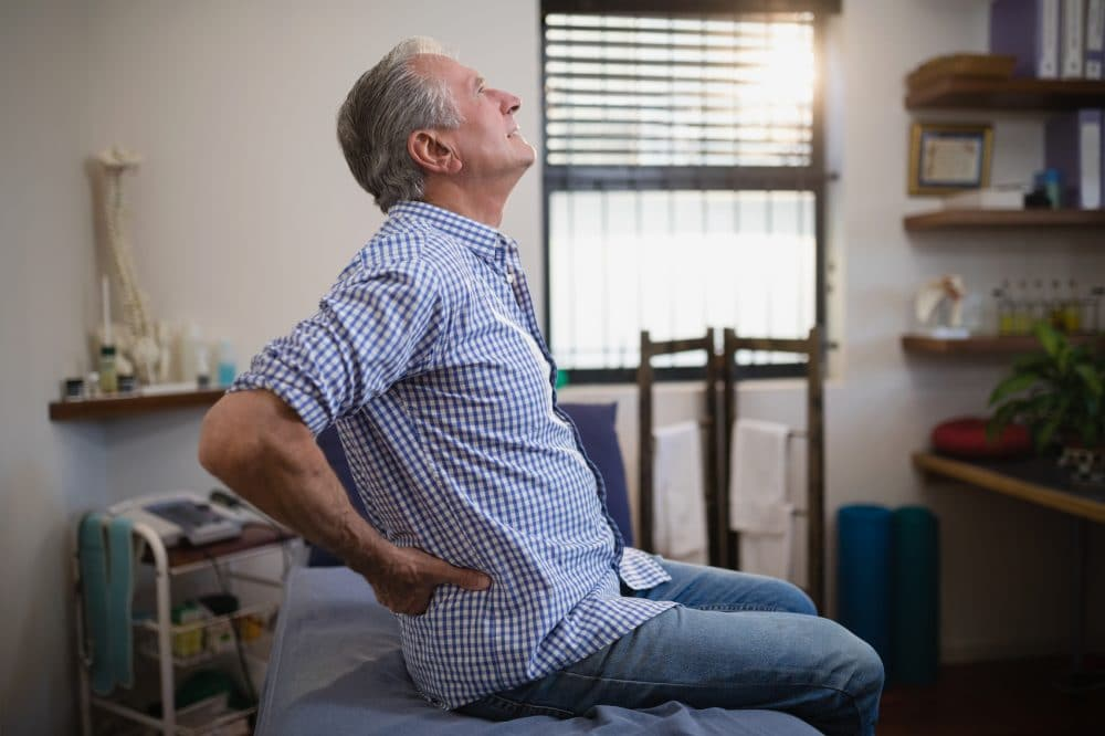 elderly man holding his buttock due to pain