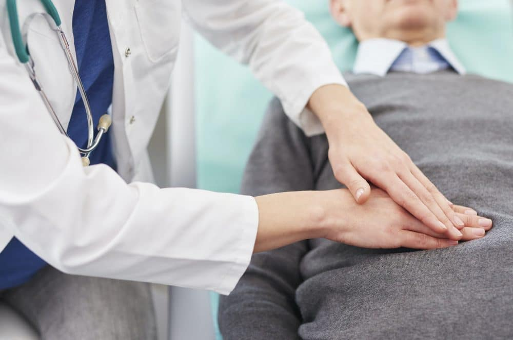doctor examining a patients stomach for a hernia