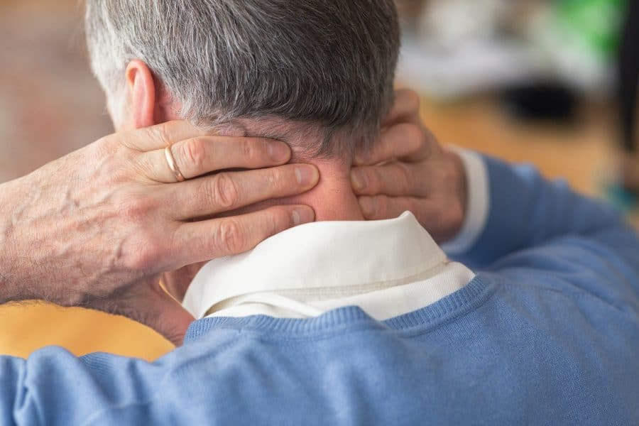 Elderly man holding his neck due to pain
