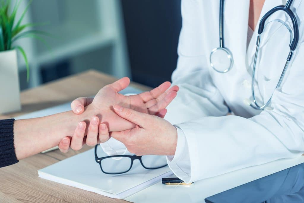 Doctor examining a patient's hand and wrist.