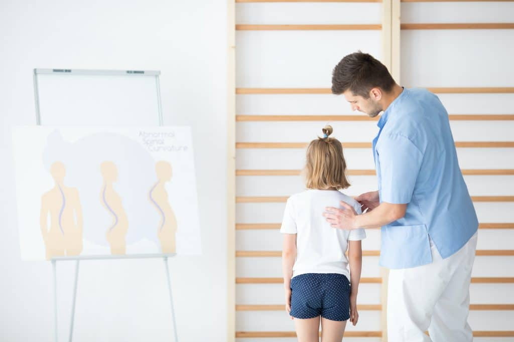 Doctor measuring the back of a girl with scoliosis