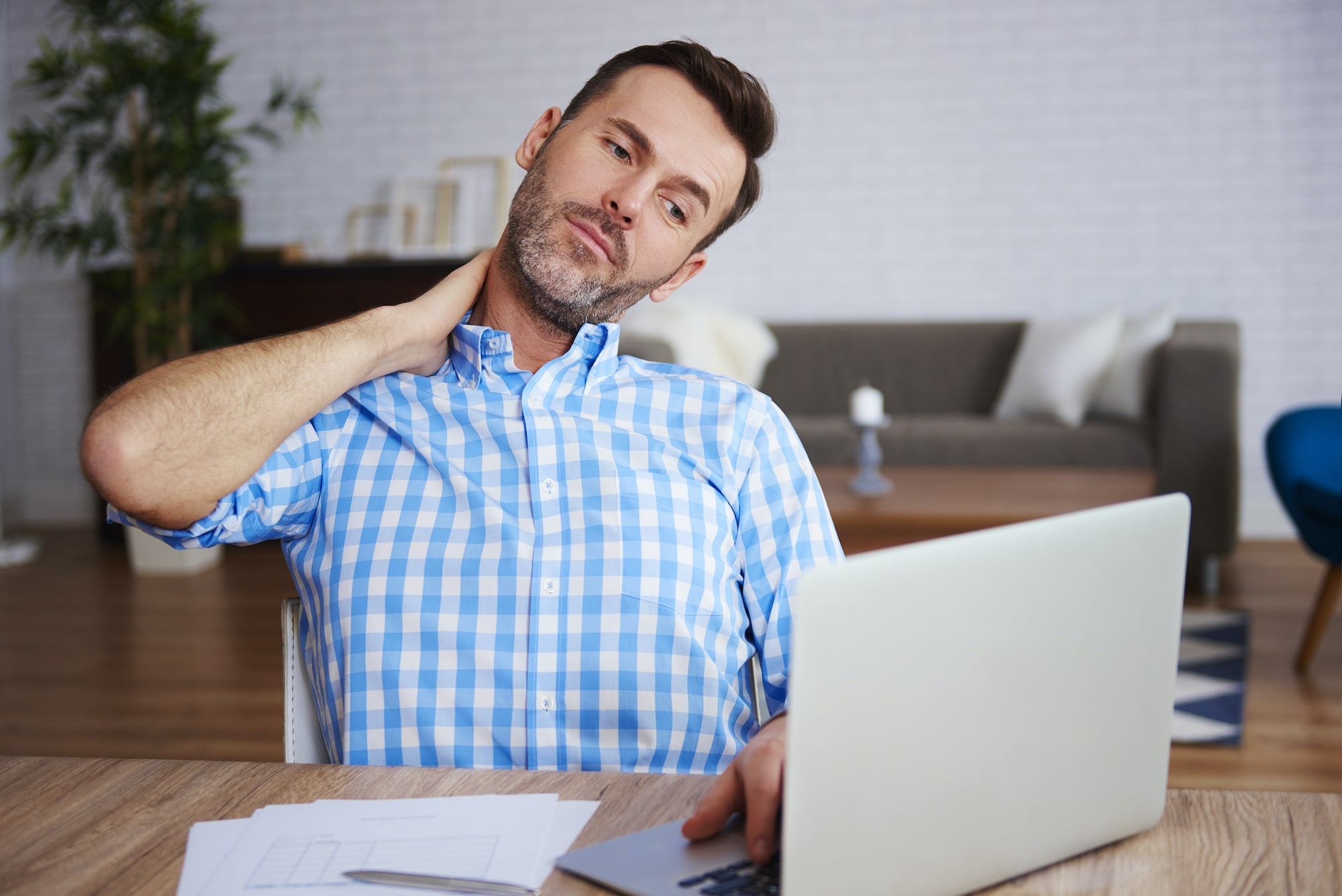 Young man holding his neck due to pain