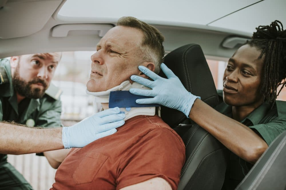 paramedics placing a neck brace on a motorist involved in a car accident