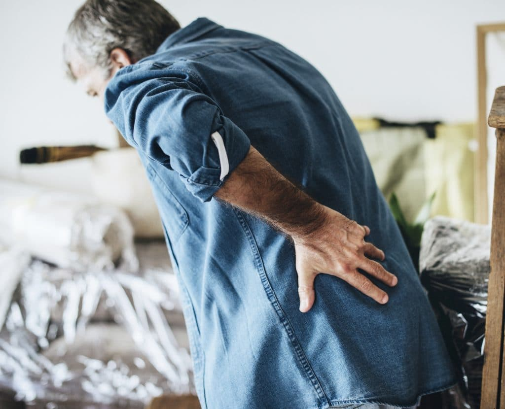 Elderly man holding his lower back due to pain.