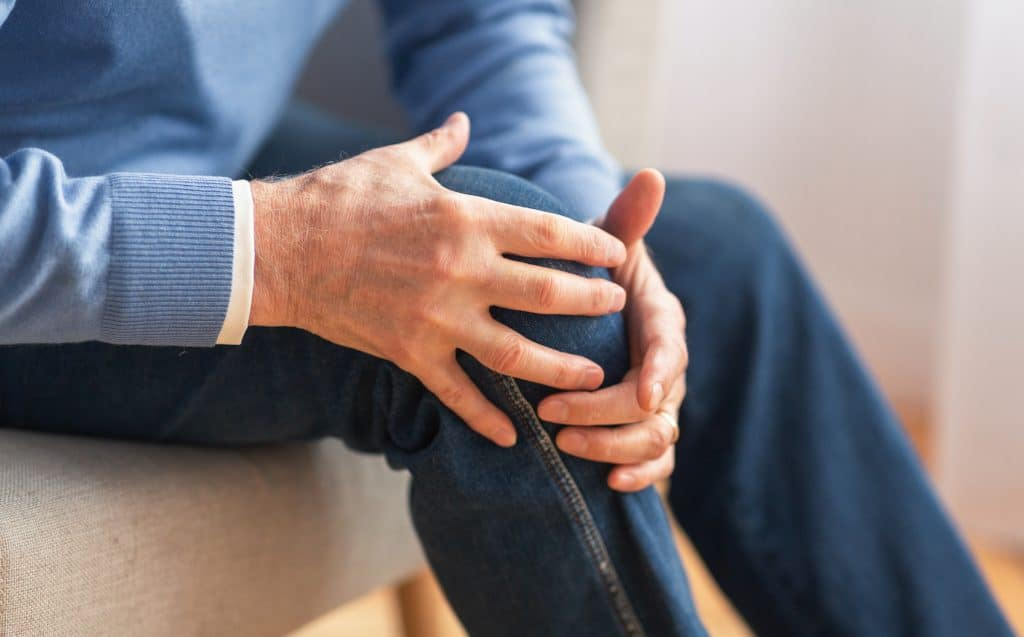 Elderly man holding his knee due to joint pain.