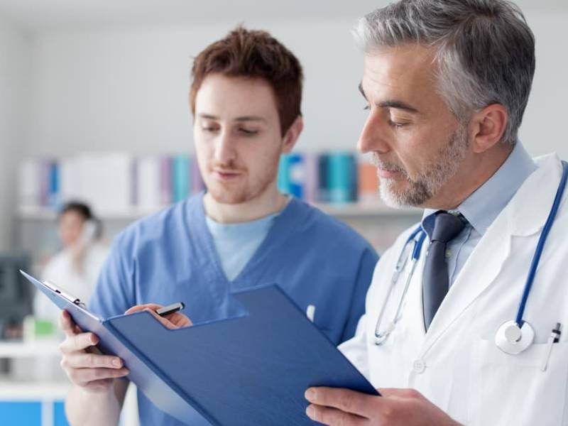 Pain management doctor in Torrance discussing with his assistant.