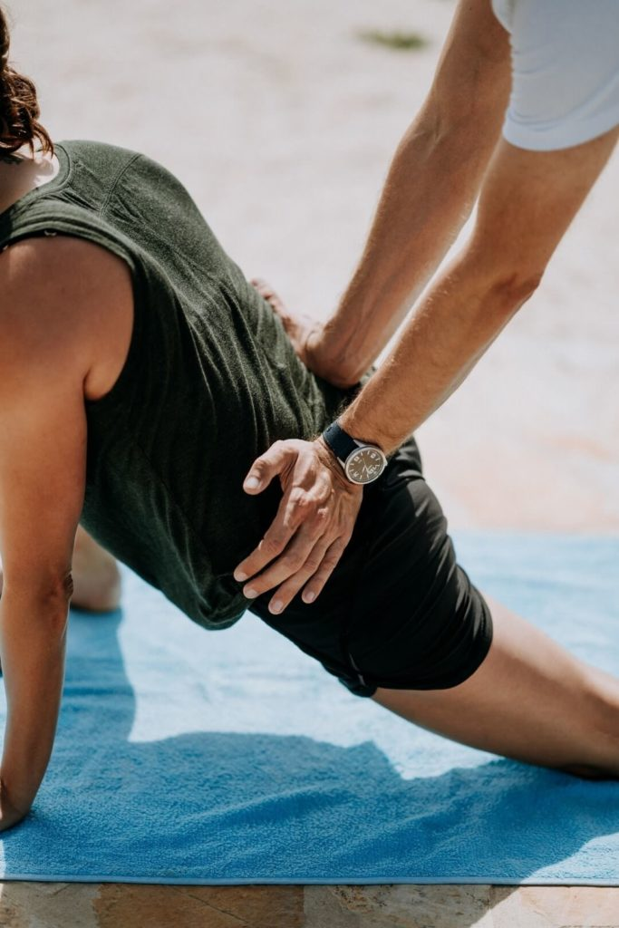 Patient performing hip exercise with a sports medicine doctor.