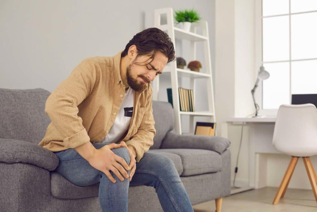 Man sitting on a sofa massaging his knee for knee pain.